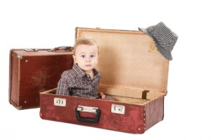 little boy sits in an old suitcase