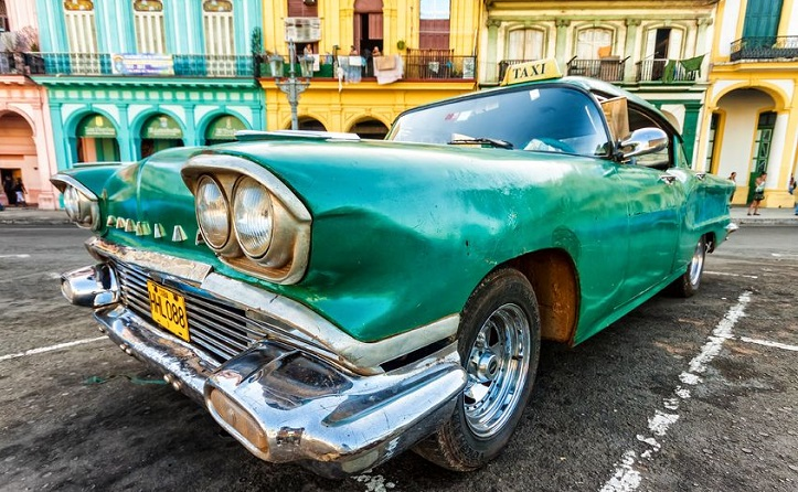 Vintage car in a colorful neighborhood in hHvana