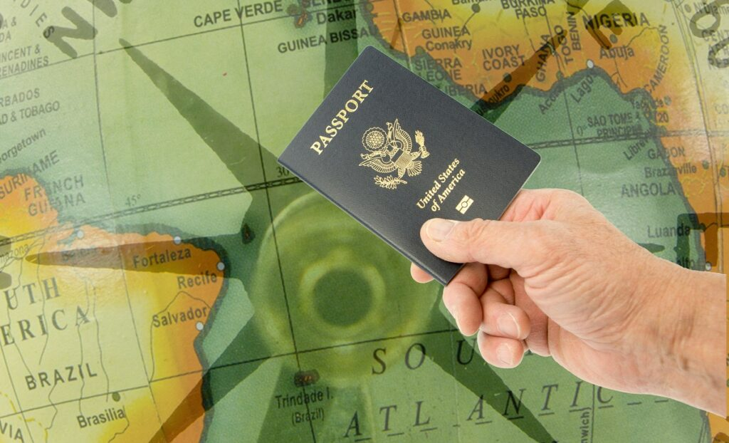 hand holding a US passport over a map of the South Atlantic